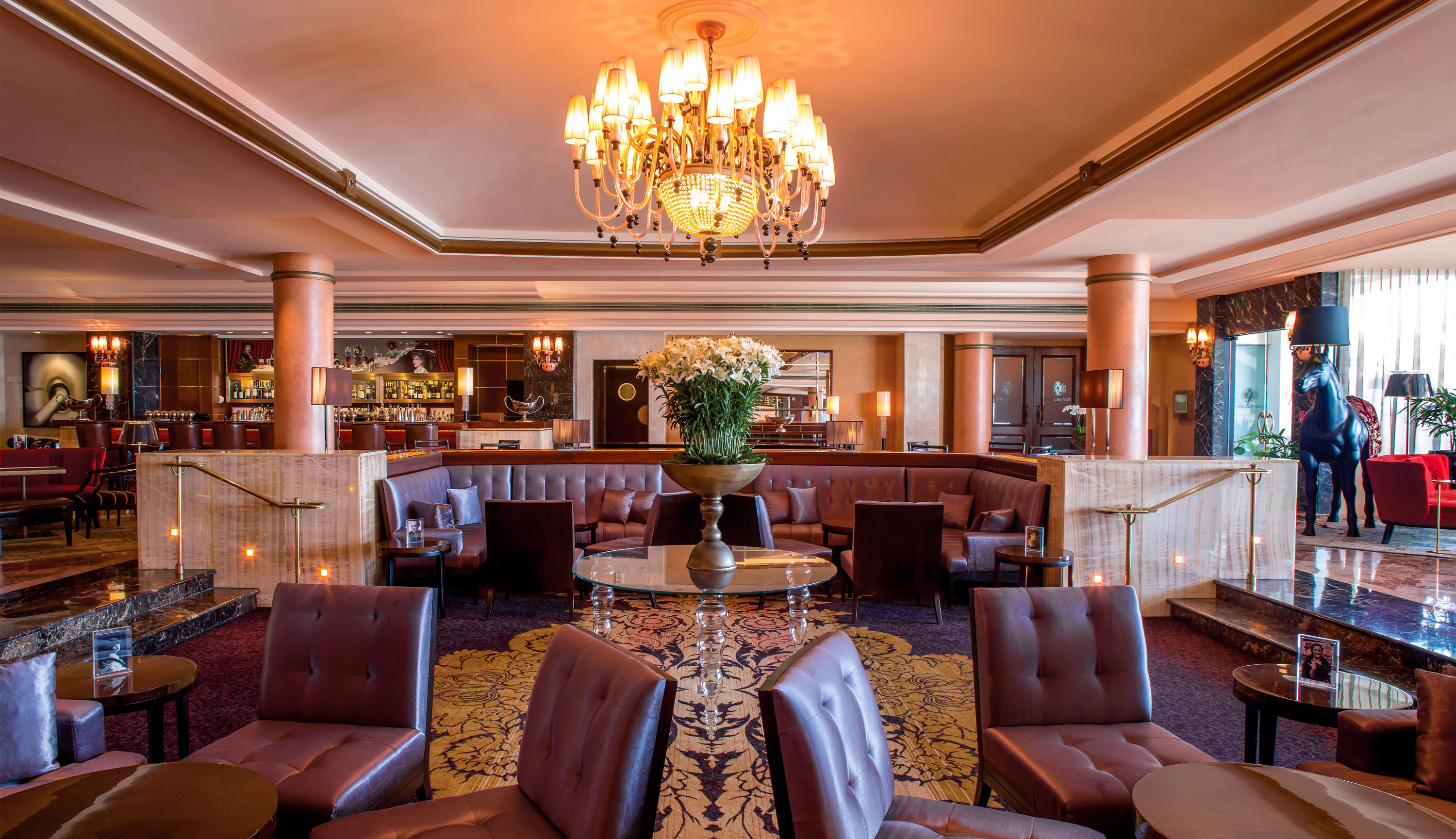 The elegant lounge at the Condado Vanderbilt hotel includes leather upholstery, marble columns and an ornate chandelier.