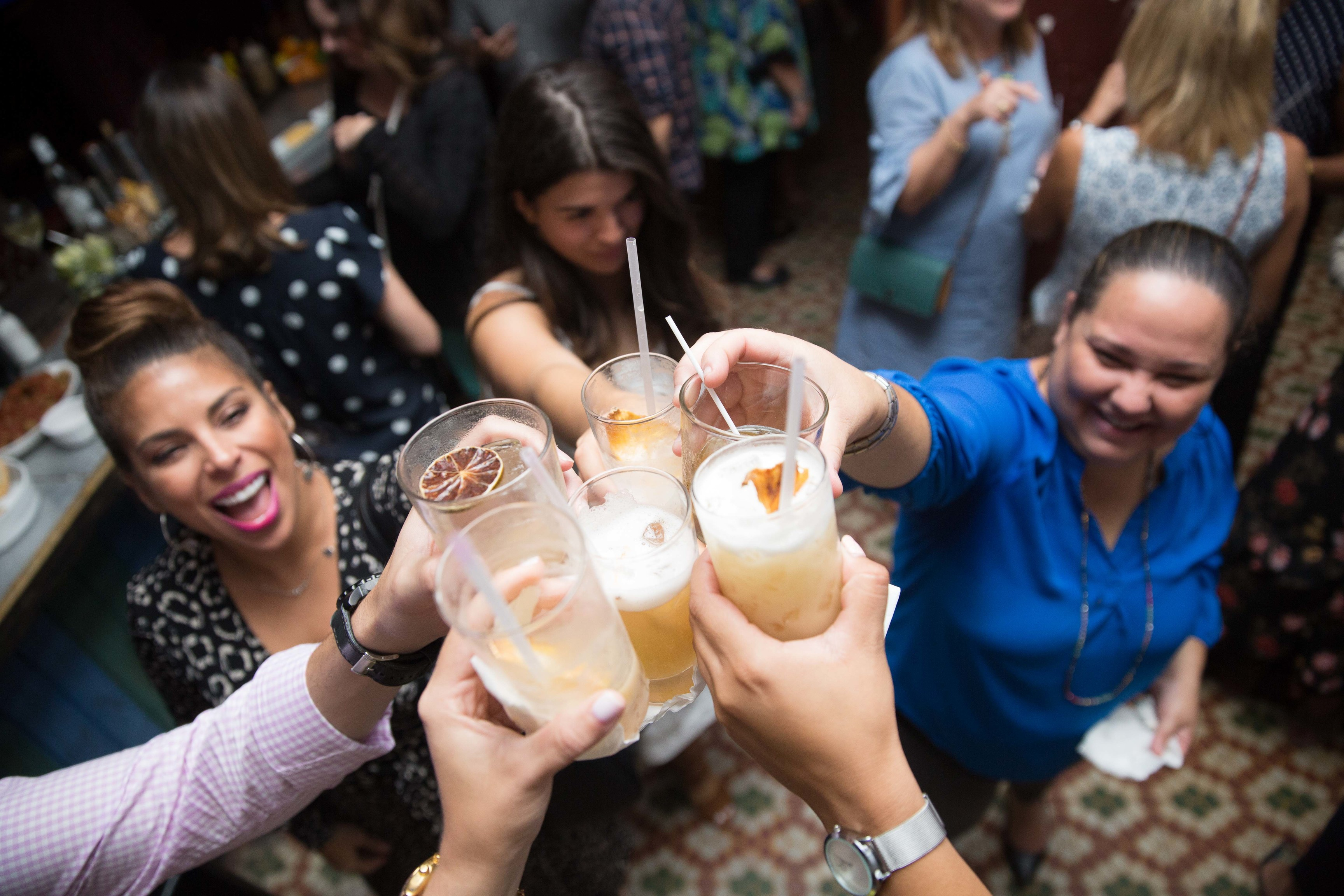 A group of friends toasts their drinks at a bar.