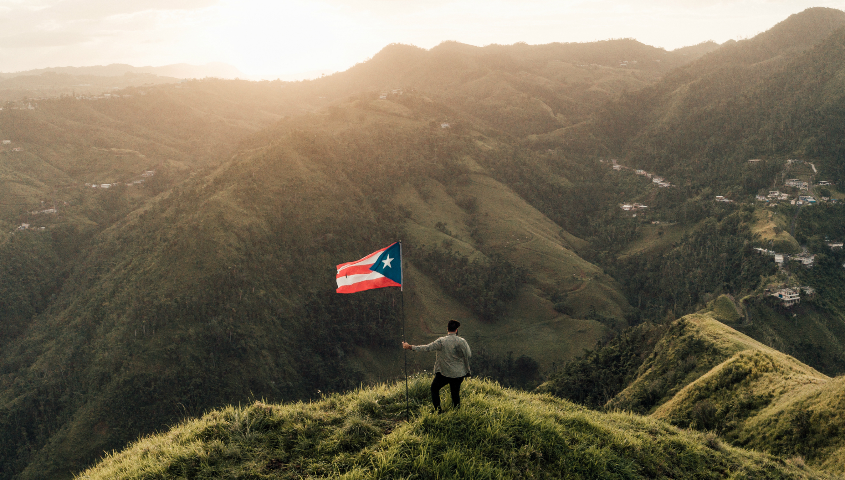 A man stands with a Puerto Rican flag atop a mountain summit as the sun sets.