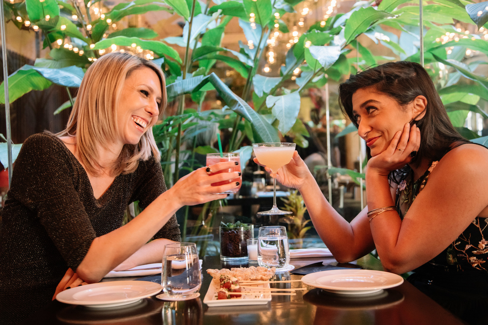 A couple enjoys craft cocktails while dining