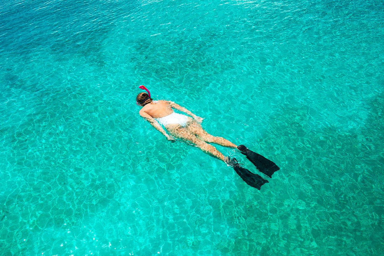 Woman snorkeling in white bathing suit against turquoise waters.