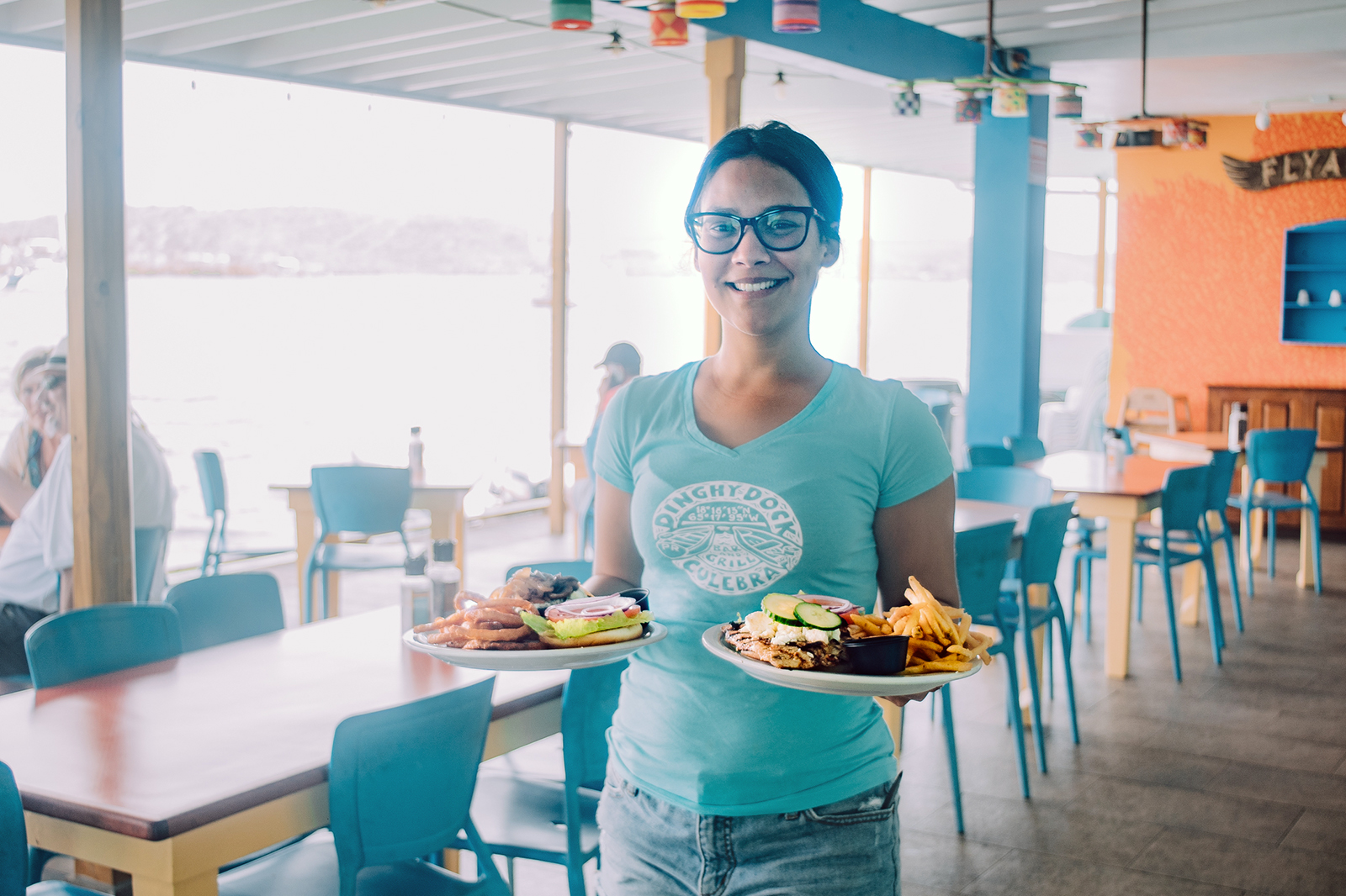A waiter holds two plates with delicious food in Culebra.