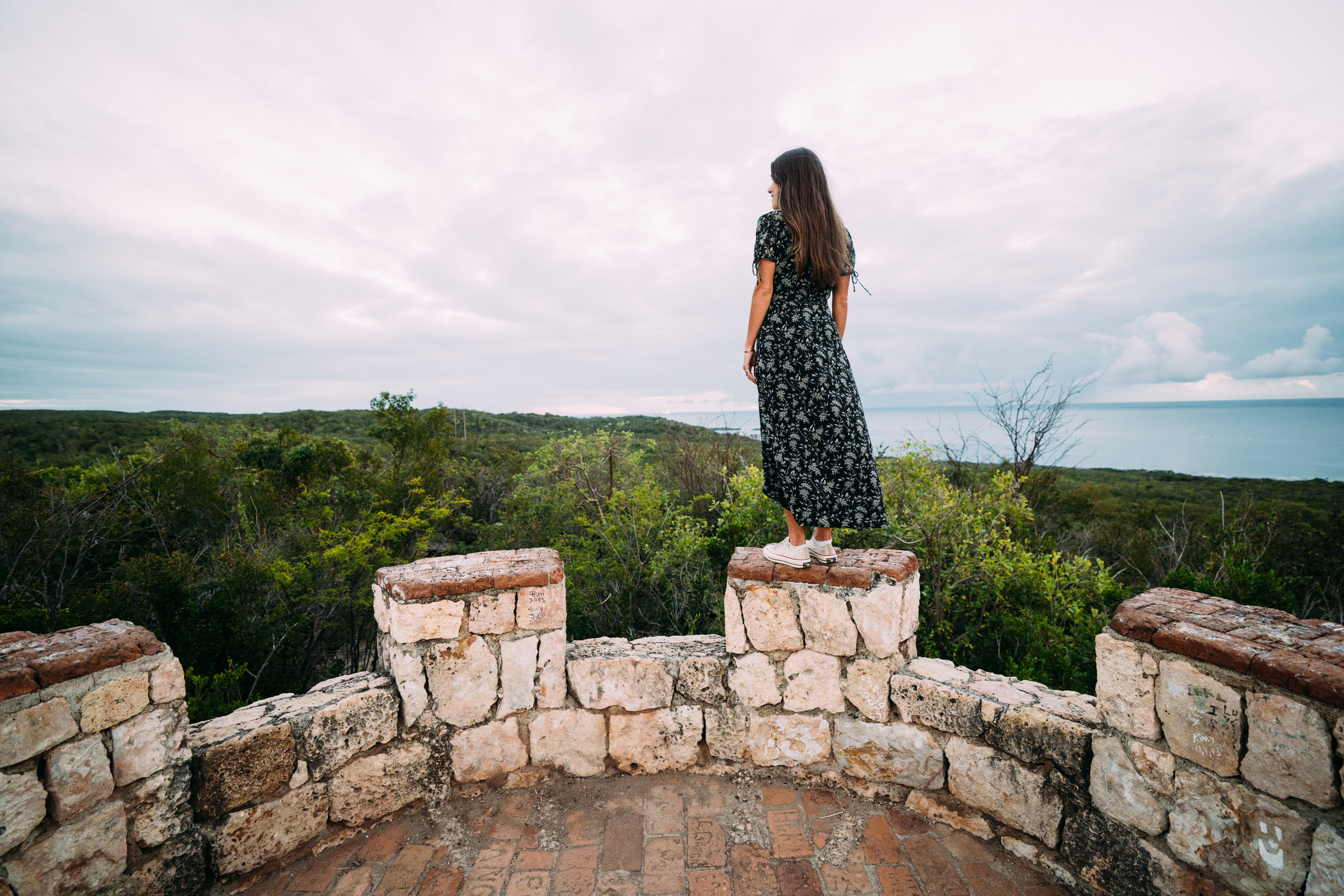 A woman peers over Guánica Dry Forest from the top of Fuerte Capron.