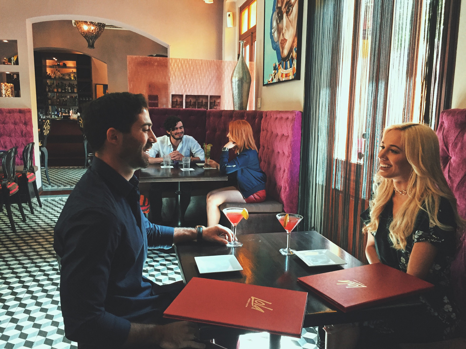 A couple enjoys their cocktails at a restaurant in Ponce.