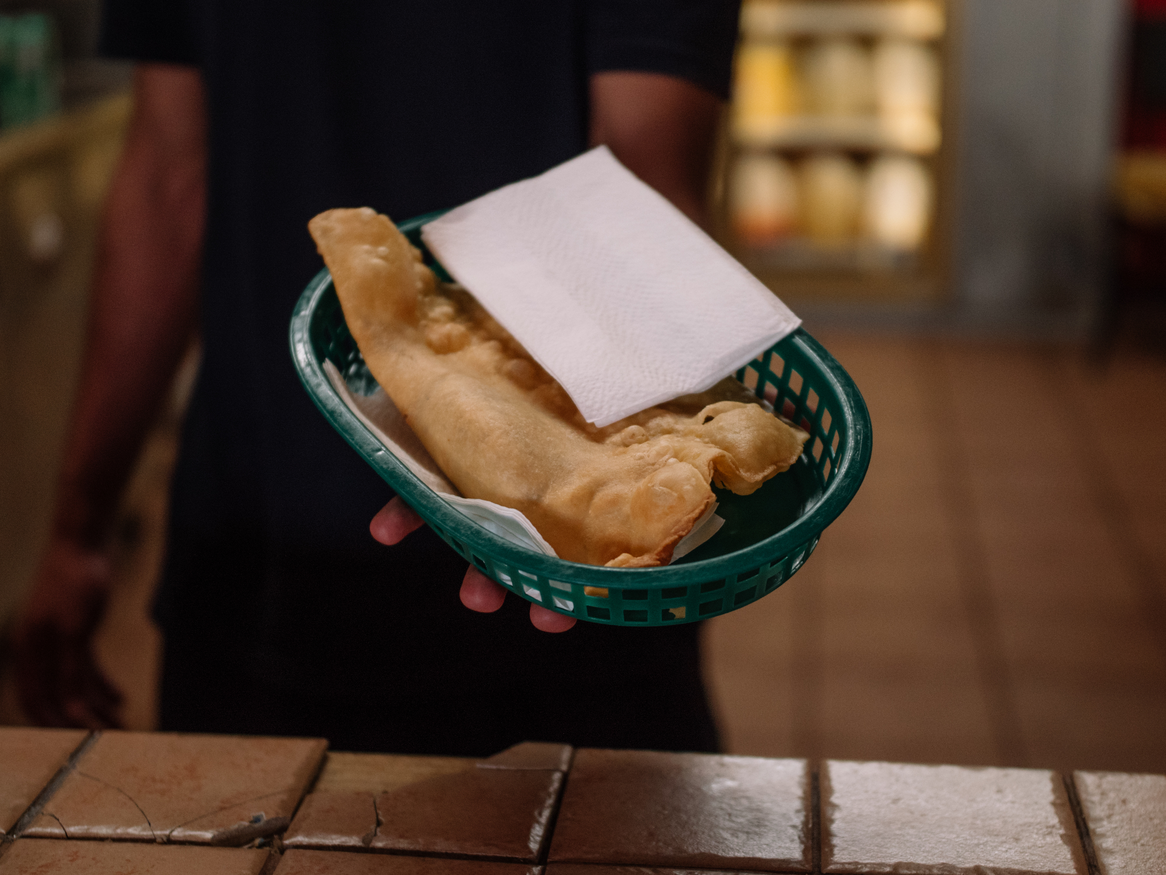 A server at Pastelillos Lamboy in Manati holds out a basket of pastelillos.