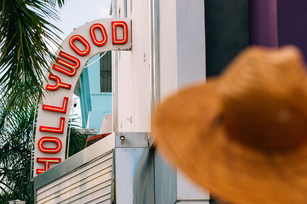 Woman in a hat standing outside the historic Hollywood Theater in Coamo.