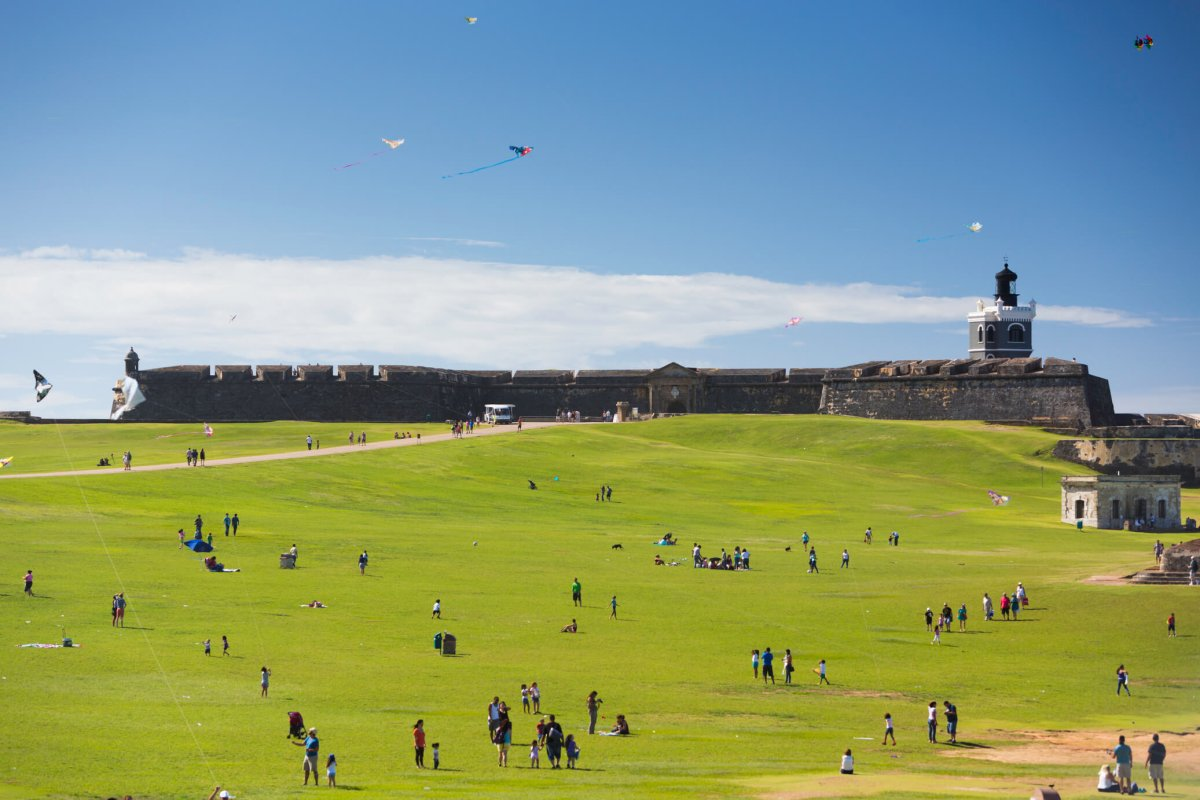 Crowds enjoying a sunny day on a field outside Castillo San Felipe del Morro in San Juan.