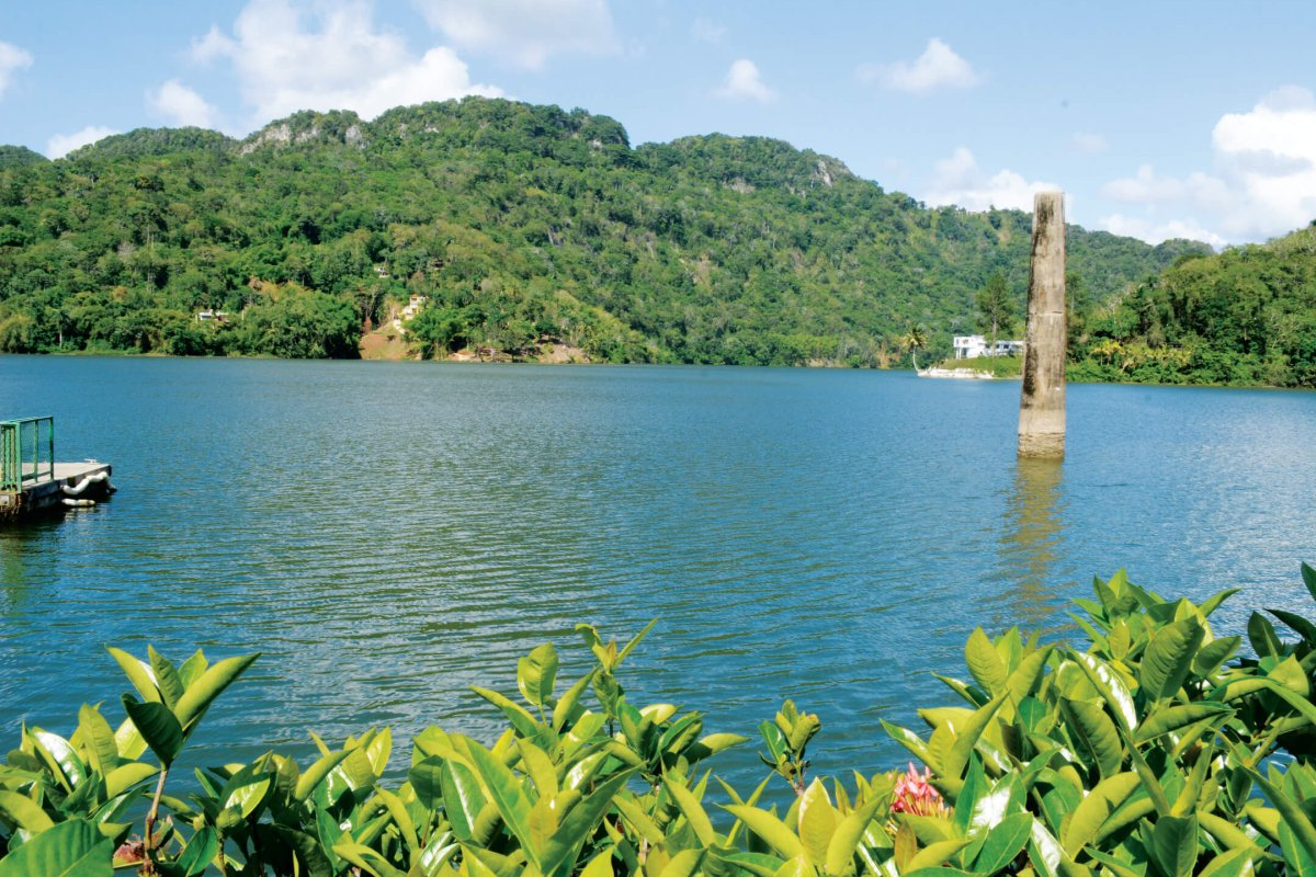 Sunny day at Lago Dos Bocas, surrounded by mountains and vegetation.