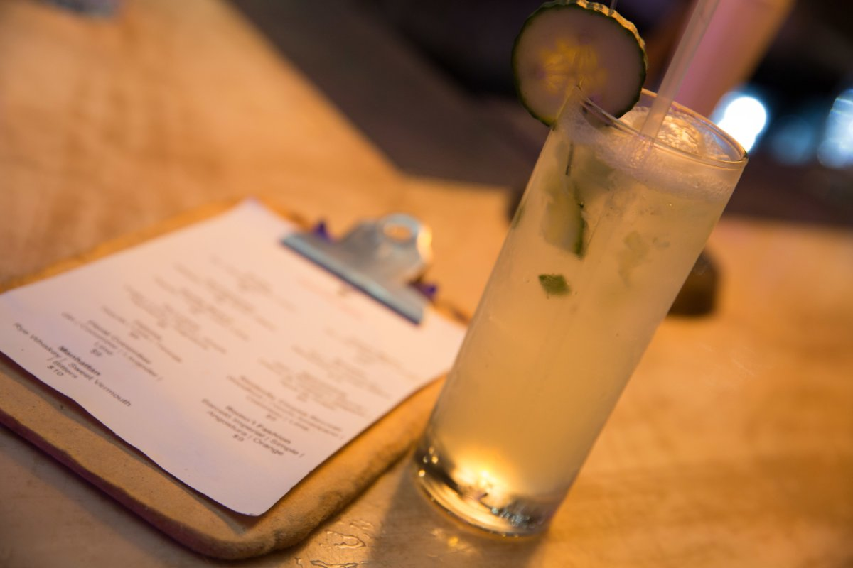 A highball cocktail next to a menu on a clipboard sitting on a table.