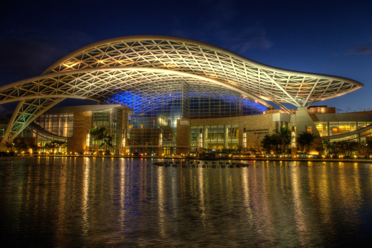 The exterior of the Puerto Rico Convention Center at night, with lights reflecting on the water.
