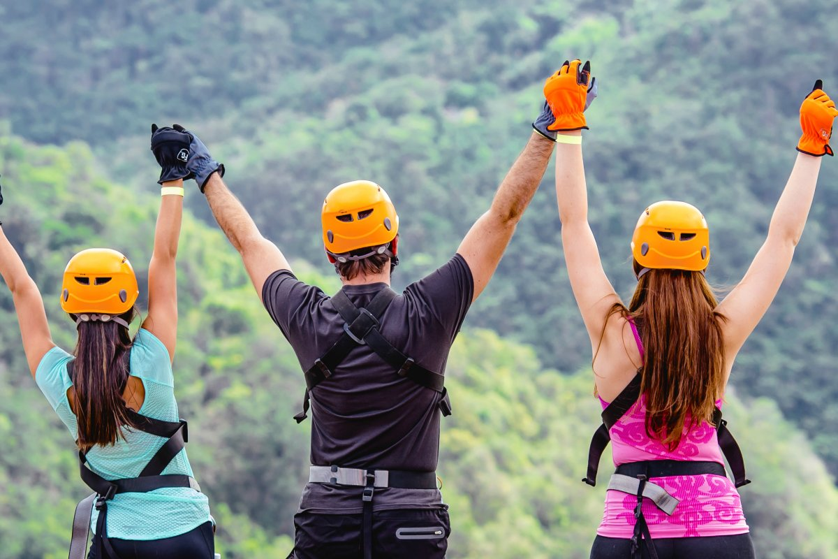 A group of people with arms raised celebrate at the top of Toro Verde Adventure Park.