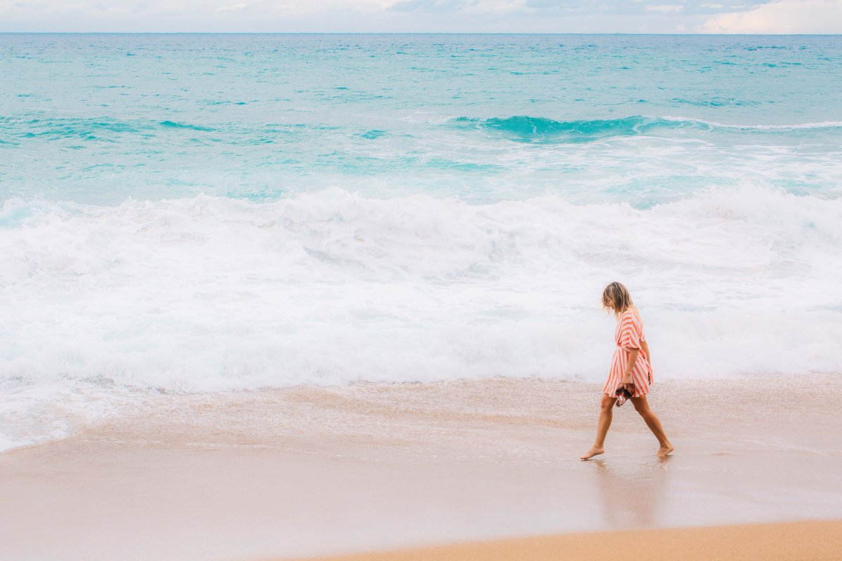 woman walking along the sand with her feet in aquamarine waves.