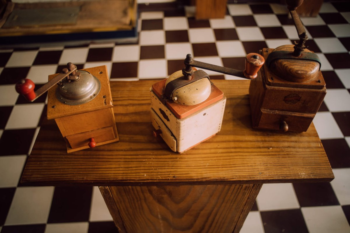 Coffee grinders sitting on a wooden table.