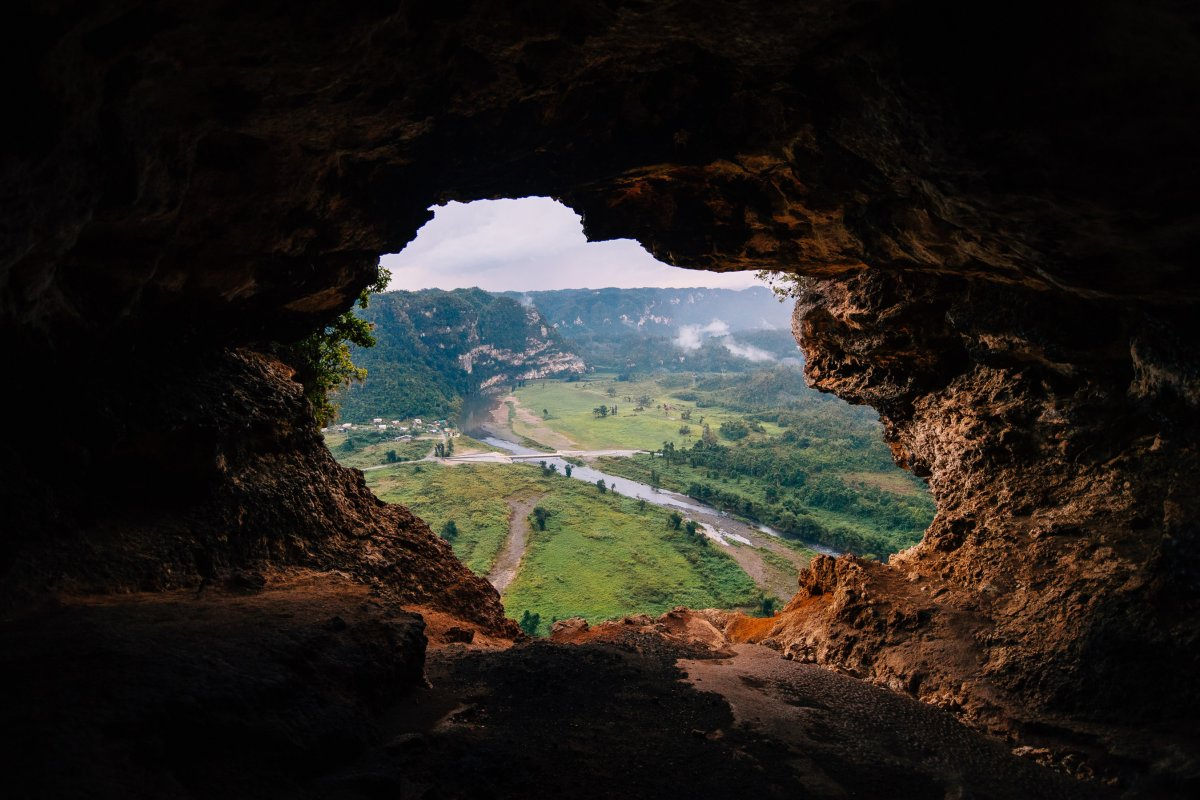 A cave opening reveals a green valley at Cueva Ventana.