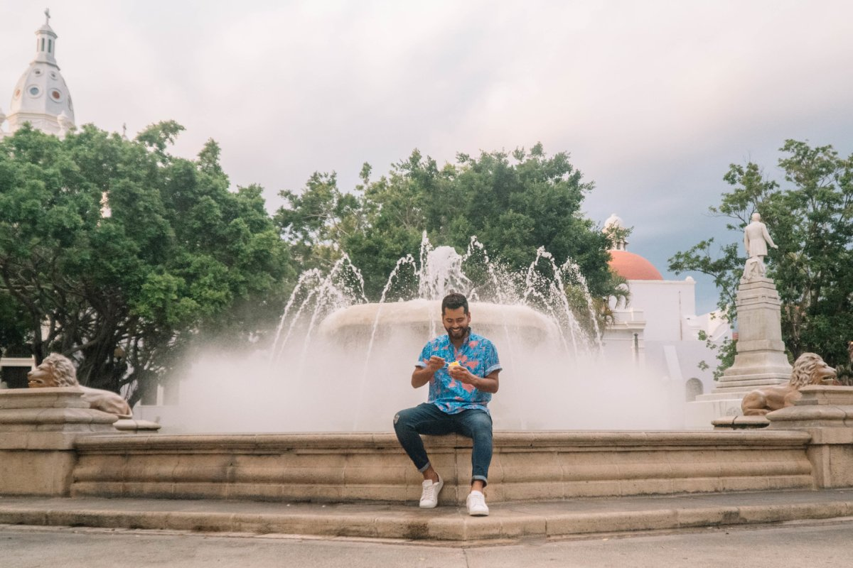 A man sits on the steps of a fountain in the Plaza las Delicias in Ponce.