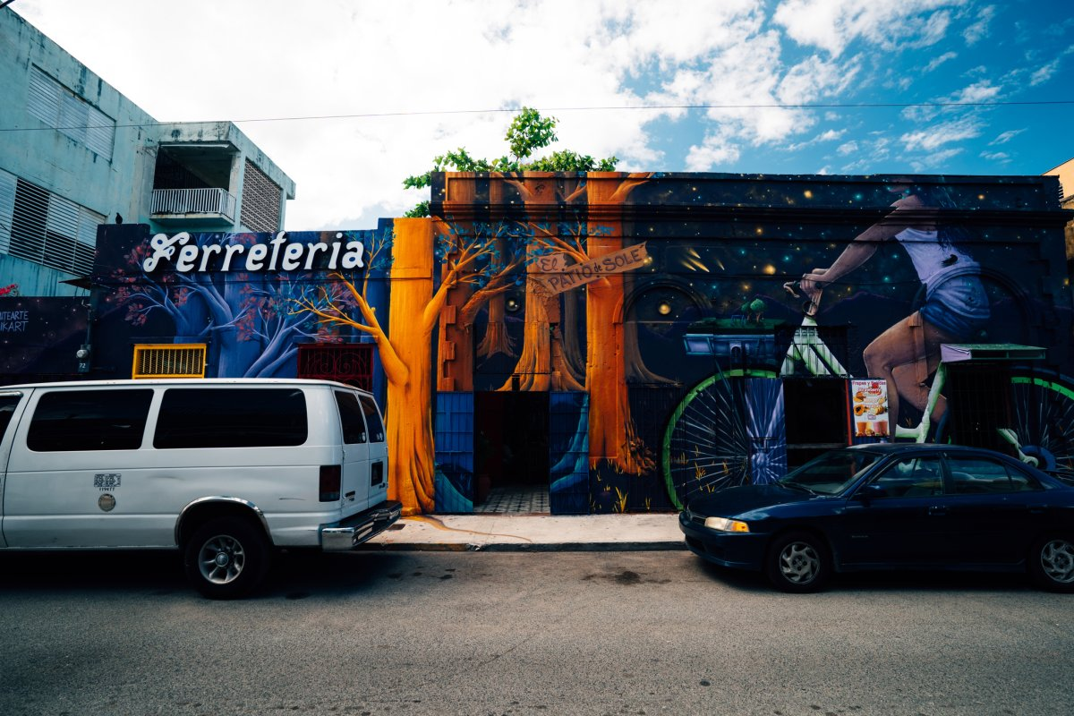 A cars parked along a street in the Santurce area of San Juan with a colorful mural on the building