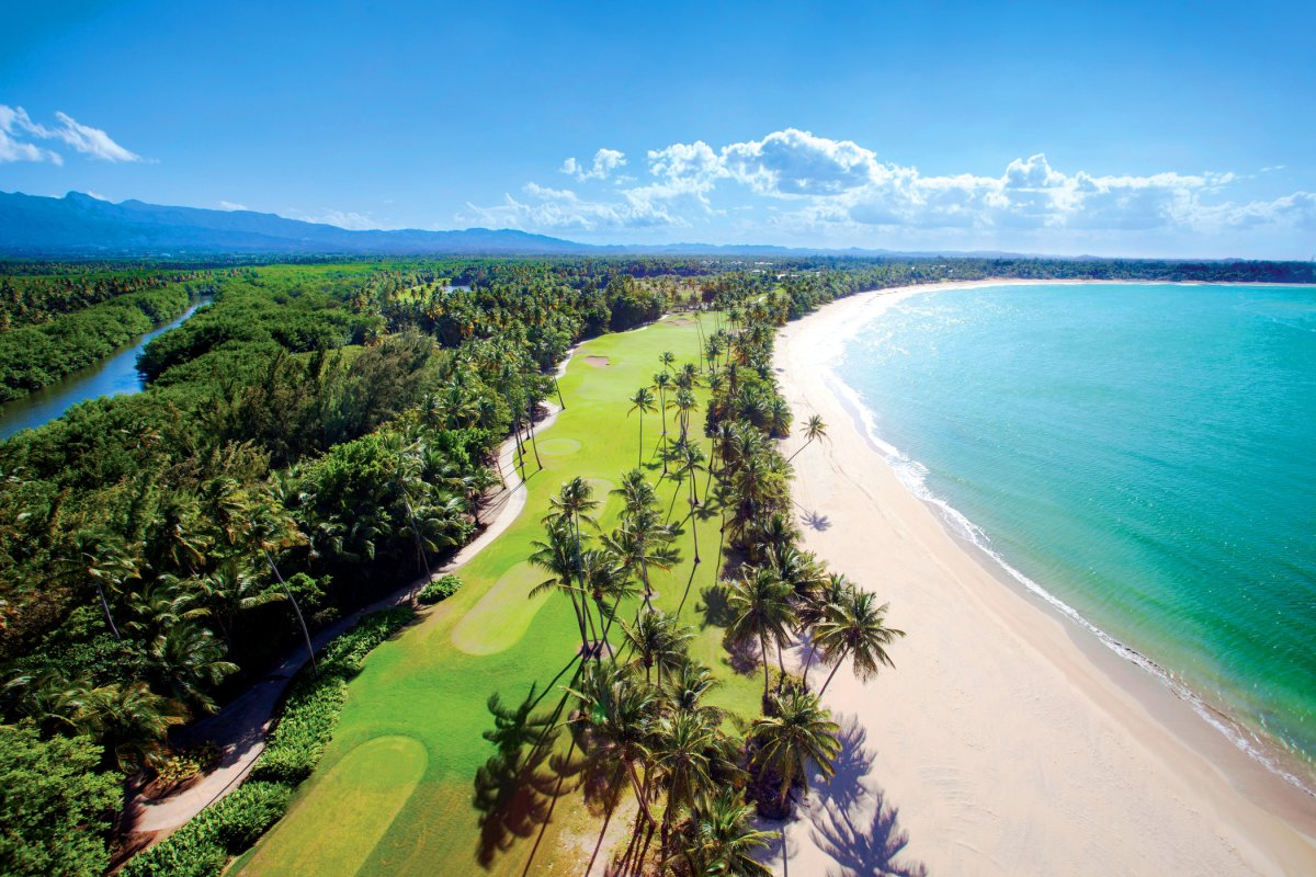 An aerial view of the St. Regis Bahia Beach golf course, nestled between the ocean and the mountains.
