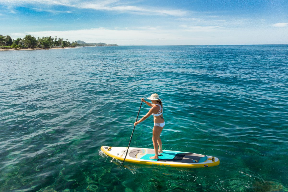 A woman enjoys stand-up paddleboarding in clear waters near Rincon.