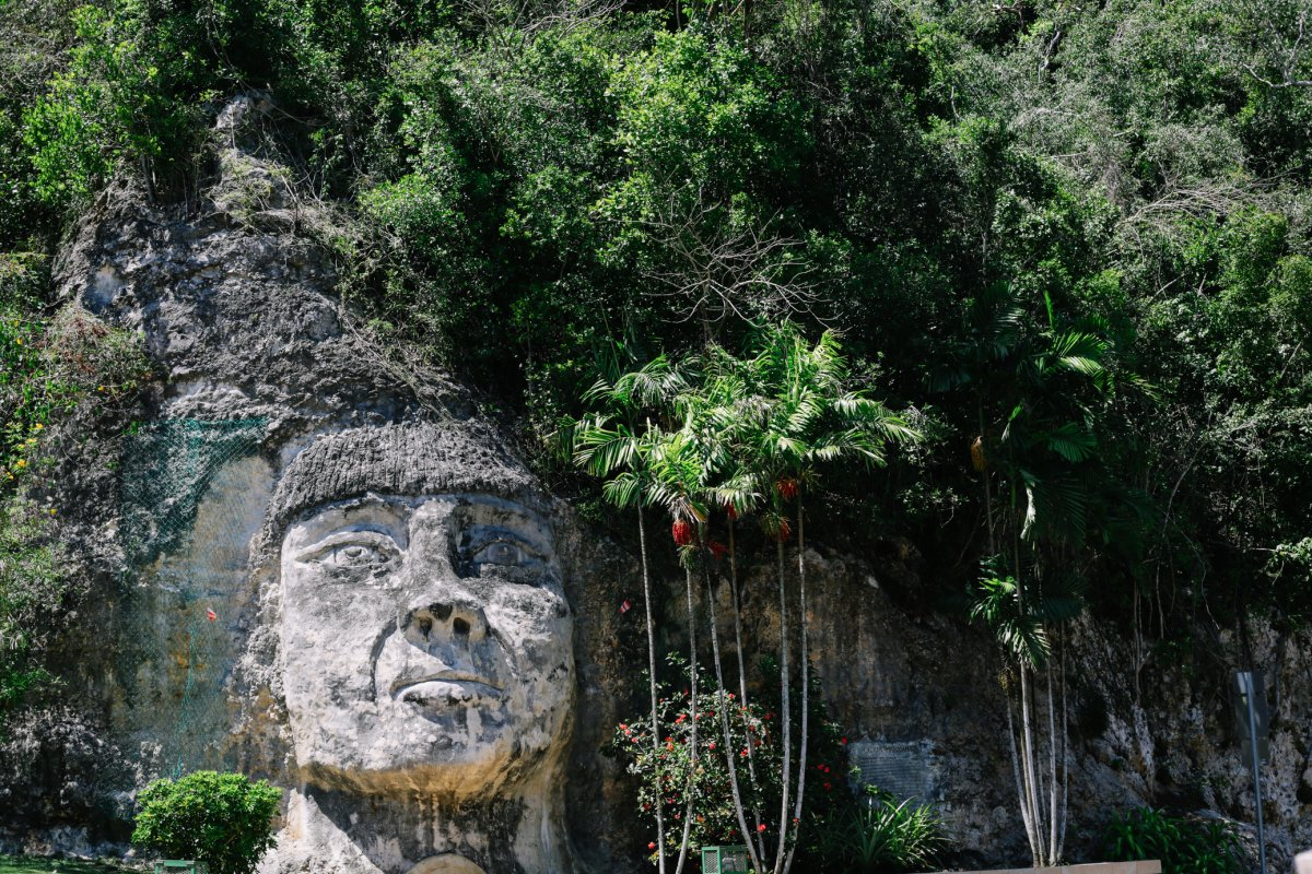 A massive face carved into the side of a steep stone cliff