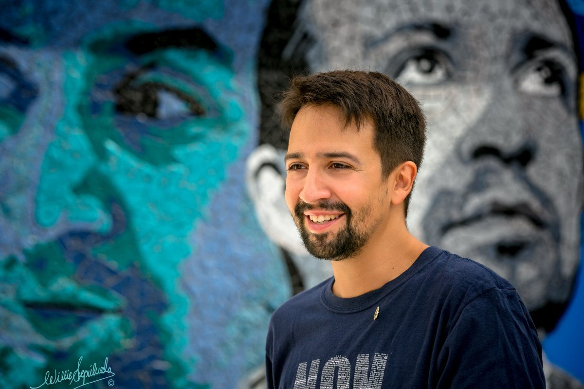 Lin-Manuel Miranda stands in front of a mural that features him as Hamilton