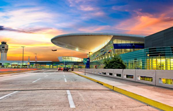 A colorful sky is visible behind the modern designed terminal building of the Luis Munoz International Airport near San Juan