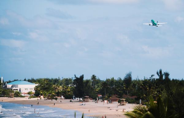 A plane departs from an airport over a beautiful beach.