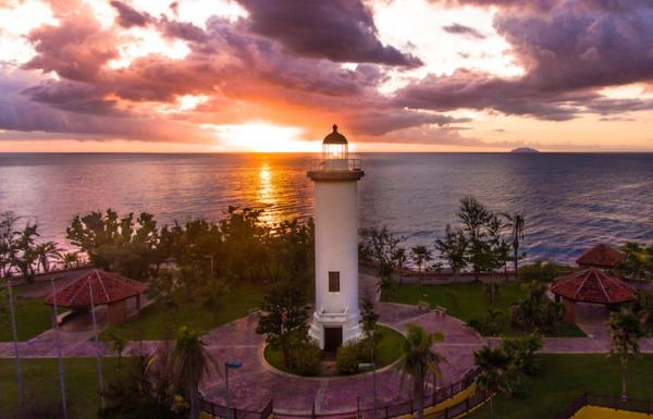 The sun sets behind a lighthouse in Rincón.