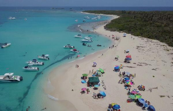 People hang out on the white sand beach of icacos island off the coast of Fajardo, Puerto Rico.