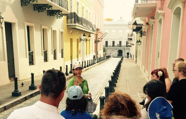 A female tour guide leads a group on a walking tour of Old San Juan.
