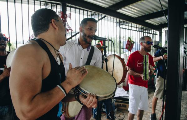 Three musicians perform Puerto Rican music.