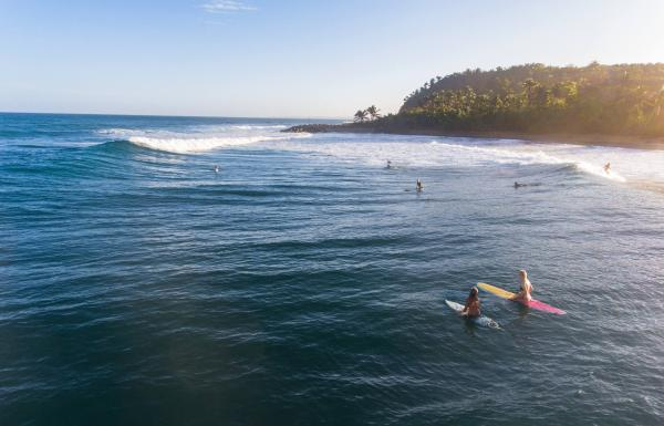 Two people waiting to catch a wave at Domes Beach in Rincon.