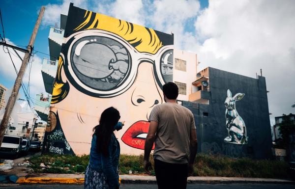 Two people admire the murals in Santurce.