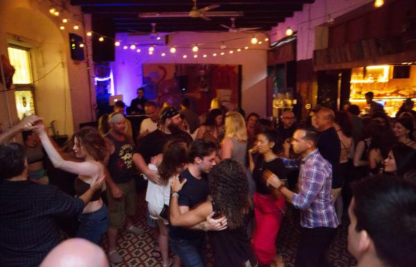 People dance and smile around La Factoria