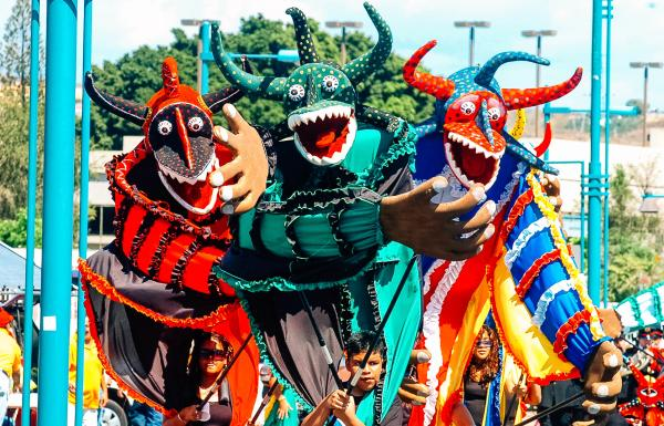 A group of large, colorful puppets in a carnaval parade in Ponce.