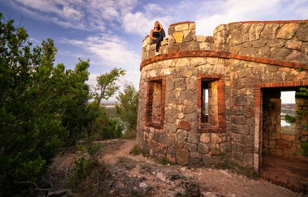 A woman sits on top of a historic fort in the Guánica Dry Forest.