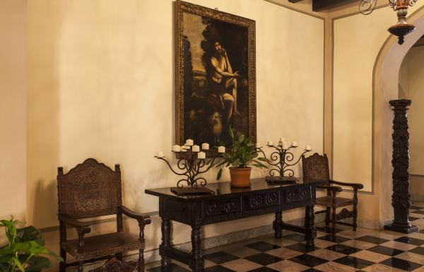 A historic painting hangs on a wall inside el convento hotel
