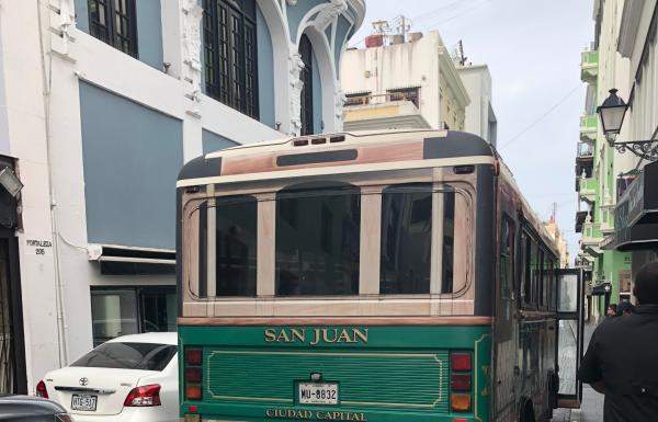 A green bus drives on a historic street in Old San Juan.