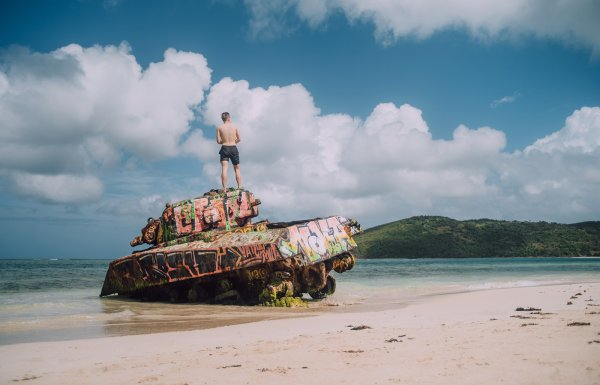 A man stands at the top of an abandoned war tank in Flamenco Beach