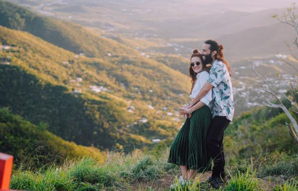 A couple embraces above a gorgeous mountain valley.