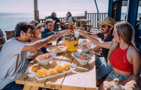 A group of friends toasts at an outdoor table overlooking the sea.