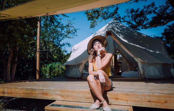 A girl sits in front of a camping tent at Pitahaya Glamping.