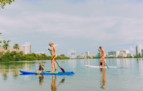 A family paddle boards at the Condado lagoon.