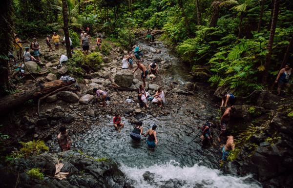 People enjoy the waterfall at Juan Diego Falls in El Yunque