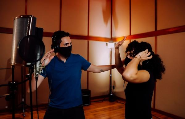 A couple enjoying reggaeton music in a studio.