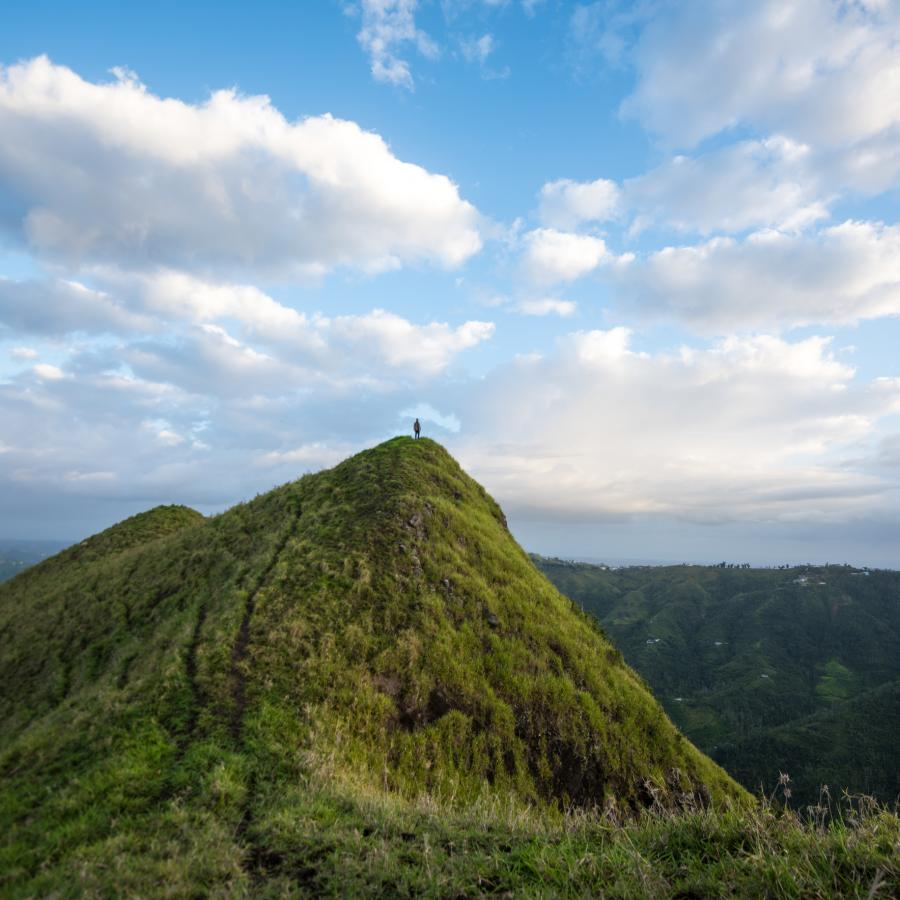 A person stands at the peak of mountain in the central region of puerto rico.