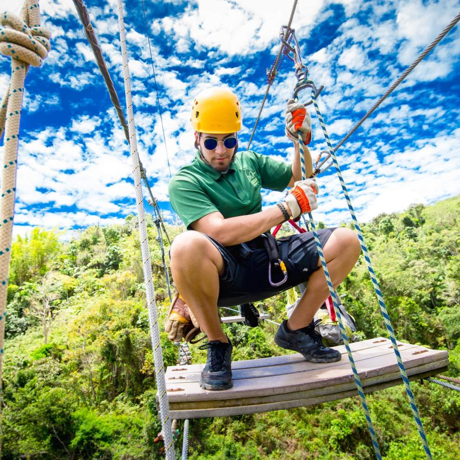 Man crouching on a suspension bridge at Toro Verde Zipline.