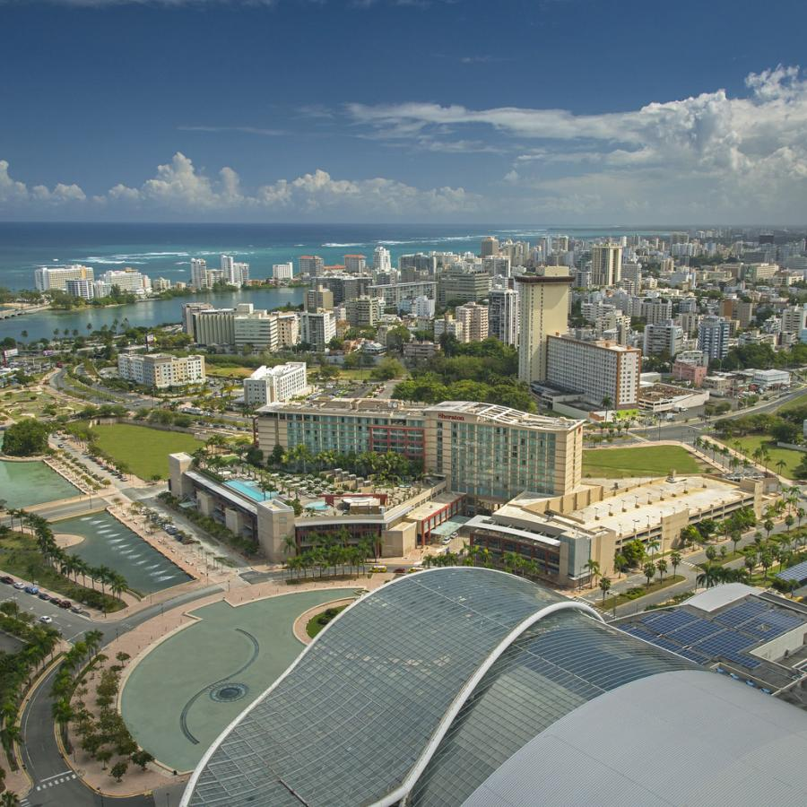 An aerial view of the Puerto Rico convention center in the foreground with the city rising in the distance.