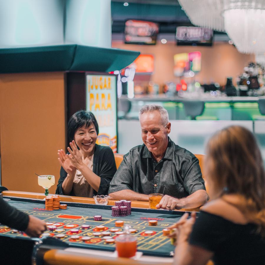 A couple celebrates their win at a casino table