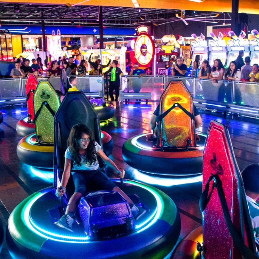 A group drives neon-glowing bumper cars at Route 66 Mall.