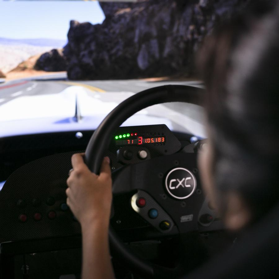 A person participates in a CXC race car simulation game at Route 66 Mall.